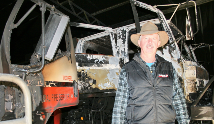 Lawrence Parrish with the gutted remains of the two fire tenders