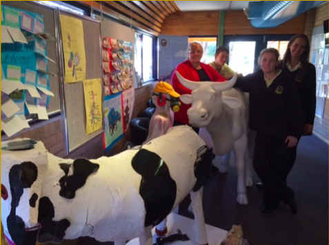 Principal Neryle Smurthwaite along with Yr 12 Ag students Emily Price, Tommy Pye & Taryn Robinson help moooving the cow to the school foyer ready for the Archibull Prize competition