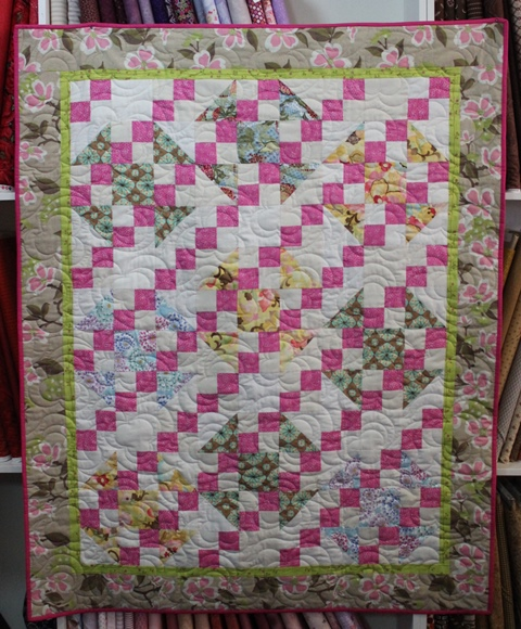 The beautiful handmade quilt hanging in The Plague and I